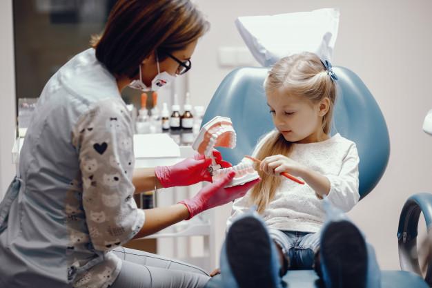 sliczny-malej-dziewczynki-obsiadanie-w-dentysty-biurze_1157-19465